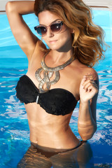 Girl tan skin necklace suite sunglasses in swimming pool