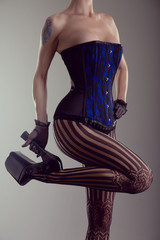 Sexy young woman wearing corset and high heel shoes