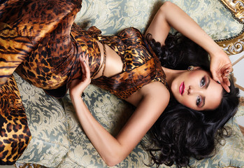 Sexy brunette woman wild animal dress accessories lying on bed