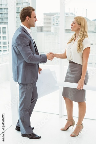 Colleagues with blueprints shaking hands - 71636731