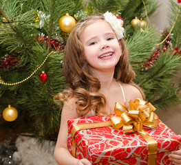 Happy adorable little girl with gift box