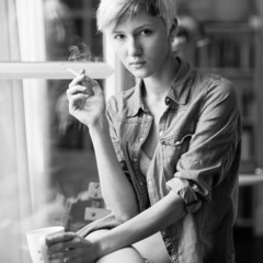 Intimate portrait of beautiful woman smoking cigarette in front