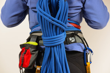 Rock climber wearing safety harness with climbing rope