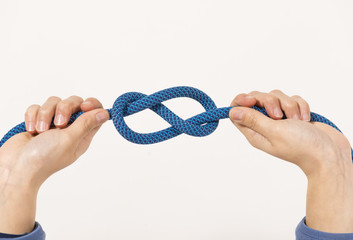 Female hands holding a climbing rope making a secure node