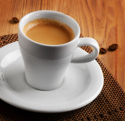 White cup of espresso coffee  on  wooden table