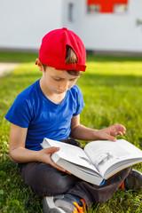 Little schoolboy read book in park
