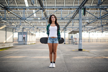 Young girl with skateboard portrait outdoors in a empty parking
