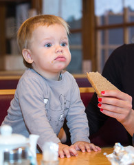 One year old boy eating rye-bread in cafe