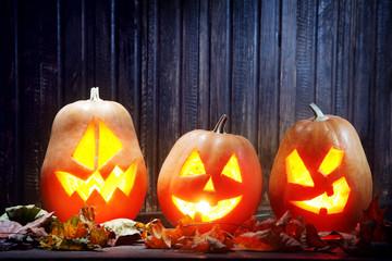 Jack o lanterns  Halloween pumpkin face on wooden background