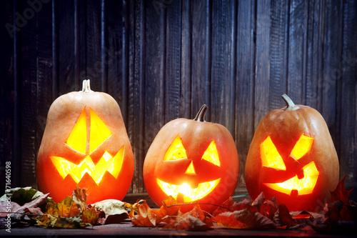 Jack o lanterns  Halloween pumpkin face on wooden background - 71640598
