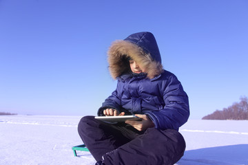 boy outdoors with tablet PC in winter snow time