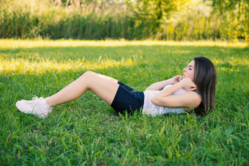 Young woman portrait practicing abdominal exercise outdoors in a