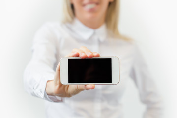 Woman showing blank mobile phone's screen horizontally