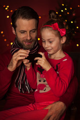 Christmas - father and daughter playing game on mobile phone