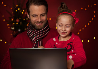 Christmas - father and daughter playing game on laptop computer