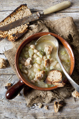 vegetables minestrone soup on bowl with toasted bread and spoon
