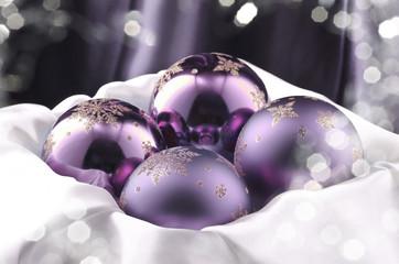 Christbaum Kugeln violett auf weißem Satin