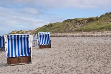 Leere Strandkörbe mit Dünen
