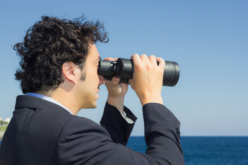 businessman looking at the sky with binoculars