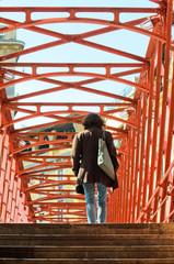 A woman crosses an iron bridge