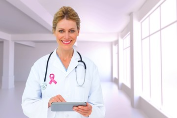 Composite image of blonde doctor using tablet pc