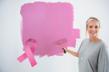 Composite image of happy young woman painting her wall pink