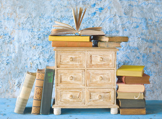 stacks of books and a small chest of drawers, free copy space