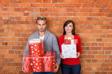 enttäuschtes paar mit vielen geschenken