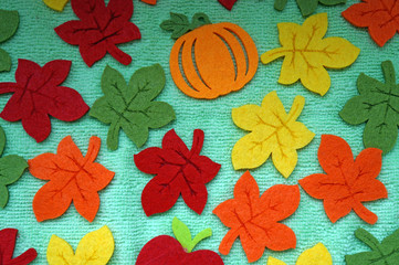 Bright Maple leaves out of felt on a light green fabric as a bac