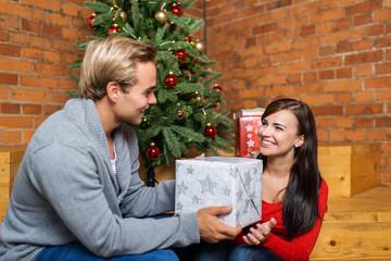 mann überreicht seiner freundin ein weihnachtsgeschenk
