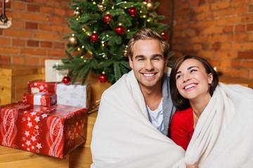 lachendes paar mit decke vor dem weihnachtsbaum