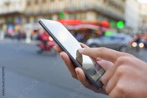 Leinwanddruck Bild Woman using her smart phone on the street in Paris