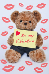 Teddy bear holding a yellow sign that says Be my Valentine