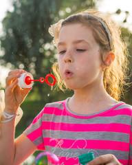 Cute little girl is blowing soap boubles