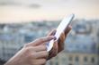 Leinwanddruck Bild - Woman using her mobile phone , city skyline background