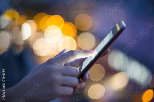 Woman using her mobile phone , city skyline night light - 71646396