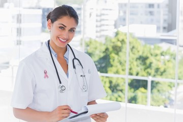 Composite image of doctor smiling and holding clipboard and pen