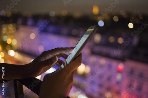 Leinwandbild Motiv Woman using her mobile phone , city skyline night light