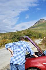 Adult man is standing near his broken car