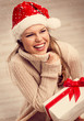 Young smiling female in Santa hat sitting with gift on the floor