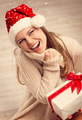 Beautiful Santa woman enjoying Christmas gift and snow