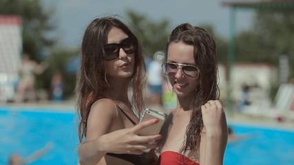 Attractive girls in sunglasses and bikini making a photo on the
