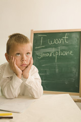 child in front of chalkboard/smartphone