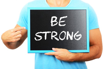 Man holding blackboard in hands and pointing the word BE STRONG