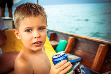 shirtless handsome boy is going to drink water on a boat