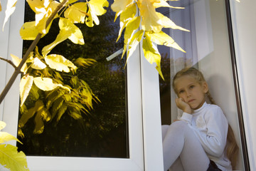 Child, girl sad sitting on a window