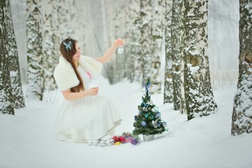 Woman decorates Christmas tree in forest