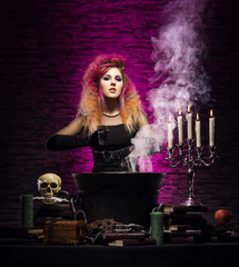 Young and beautiful witch making witchcraft in the dungeon