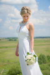 Young bride with bouquet on nature