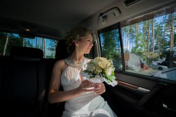 Bride with bouquet sitting in wedding car